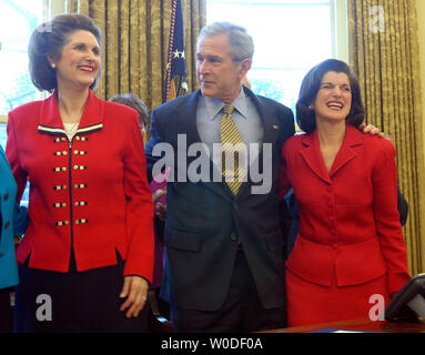 U.S. President George W. Bush greets Lynda Bird Johnson Robb (L) and Luci Baines Johnson, President Johnson's daughters,  after signing H.R. 584, the Lyndon Baines Johnson Department of Education Building bill, in the Oval Office of The White House on March 23, 2007.    (UPI Photo/Roger L. Wollenberg) - Stock Photo