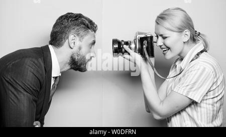 He is photogenic. Pretty woman using professional camera. Businessman posing in front of female photographer. Photographer shooting male model in studio. Fashion shooting in photo studio. - Stock Photo