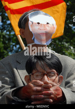 A protester wearing a mask in the likeness of Vietnamese President Nguyen Minh Triet holds his hands over the mouth of another protester during a demonstration in Lafayette Park across the street from the White House on June 22, 2007. Triet is set to meet with U.S. President George W. Bush today.   (UPI Photo/Roger L. Wollenberg) - Stock Photo
