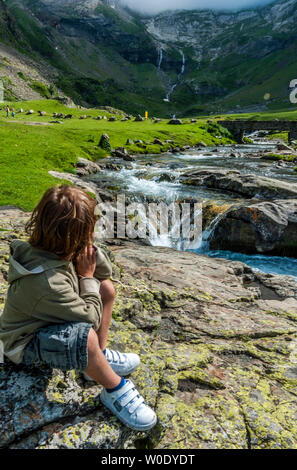 France, Hautes-Pyrenees, Pyrenees National Park, Cirque de Troumouse (UNESCO World Heritage). A little boy sat on a rock observes a torrent running. - Stock Photo