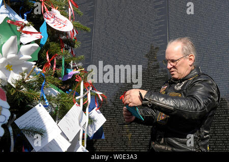 Mike Akins, 62, of Woodbridge, Virginia, helps to decorate a Christmas tree at the Vietnam Veterans Memorial on the National Mall in Washington on December 20, 2007. Akins' brother Steven Townsley was killed in Vietnam. The tree was decorated with cards, sent by Americans, containing messages for those remembered on the Wall as well as active-duty military personnel.   (UPI Photo/Roger L. Wollenberg). - Stock Photo