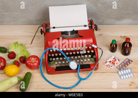 Doctor workplace with medical prescription on typewriter - choice between natural vitamins, vegetables, fruits and berries or tablets and pills on woo - Stock Photo