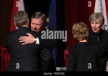 U.S. President George W. Bush hugs former Attorney General John Ashcroft following his remarks at the Republican Governor's Association at the Nation Building Museum in Washington on February 25, 2008. First Lady Laura Bush shakes hands with Ashcroft's wife, Janet, at right. (UPI Photo/Ken Cedeno) - Stock Photo