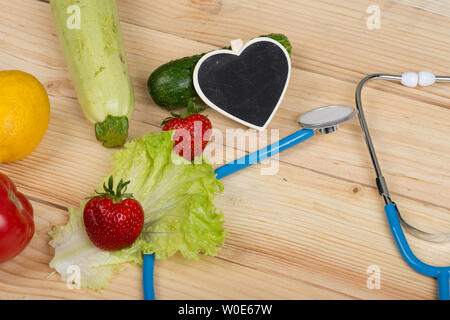 Good healthy and diet concept - Blackboard in shape of heart, stethoscope and vegetables, fruits and berries on wooden table - Stock Photo