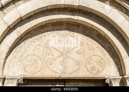 France, Pyrénées National Park, Val d'Azun, Aucun, Roman great door of the church (Monument historique, French designation given to some national heritage sites), chrismons surrounded by the paschal lamb and birds - Stock Photo