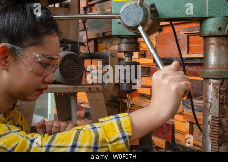 Women standing is craft working drill wood at a work bench with Drill Press power tools at carpenter machine in the workshop - Stock Photo