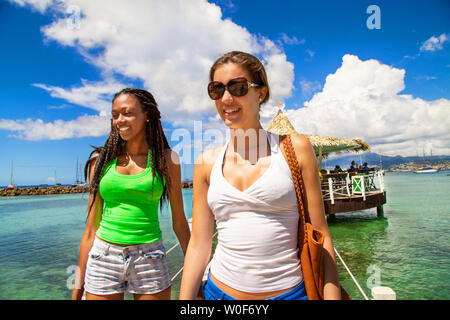2 smiling girlfriends walking on a footbridge coming from a bar on stilts on a Caribbean beach in a paradisiacal landscape. - Stock Photo