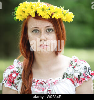 Portrait of a red-haired freckled woman in a wreath - Stock Photo