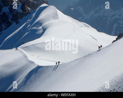 France, haute savoy, Chamonix, Mont blanc range, some alpinists are hiking on the snow edge of the aiguille du midi - Stock Photo