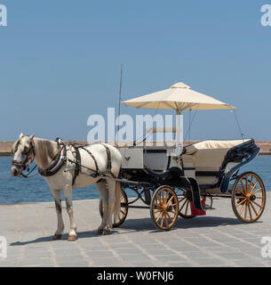 Chania, Crete, Greece, June 2019. Horse drawn carriage waiting on the Old Venetion Harbour in Chania to take passengers on a ride. - Stock Photo