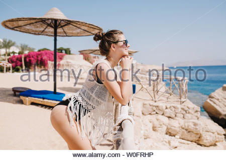 Graceful slim girl in swimsuit and knitted mantle standing on hotel beach , enjoying sun and fresh ocean air. Gorgeous shapely young woman resting on the sea resort and posing, looking at the horizon - Stock Photo