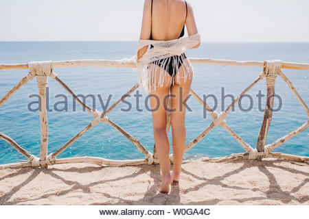 Graceful girl in black bikini and knitted pareo resting outside and posing on sea background in warm sunny morning. Beautiful shapely young woman in swimsuit standing in front of ocean - Stock Photo
