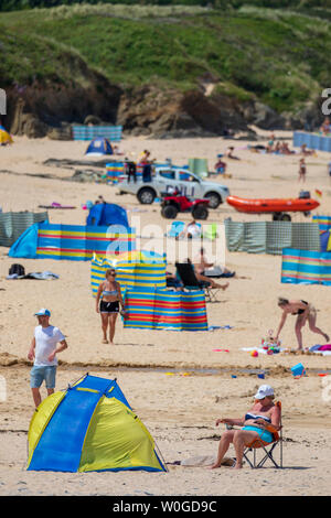 Cornwall, England, UK. UK Weather: Thursday 27th June 2019. Hot sunshine arrives along with heatwave temperatures with car thermometers showing 31C along the Cornish coastline. Beach goers enjoying the hot sunshine during heatwave temperatures at Harlyn Bay Beach near Padstow, Cornwall - Stock Photo