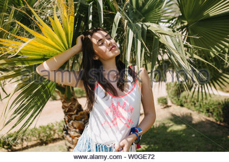 Irresistible girl with dark straight hair resting in shade of palm trees enjoying vacation in exotic country. Portrait of cute young woman posing with eyes closed with southern plants on background - Stock Photo
