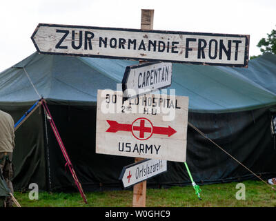 Signposts at a recreation of a U.S. Army camp for the remembrance of the D-Day invasion and liberation of France - Stock Photo