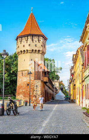 SIBIU, ROMANIA - AUGUST 28, 2017: Tourist couple in a Sibiu street next to the Carpenters' Tower, Turnul Dulgherilor - Stock Photo
