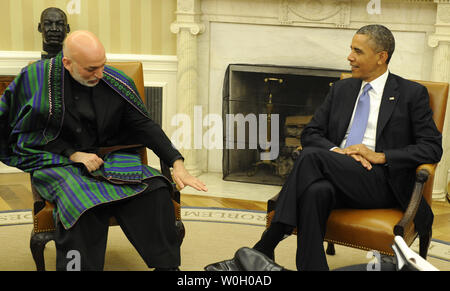 US President Barack Obama (R) listens to Afghan President Hamid Karzai who gestures during a bilateral meeting in the Oval Office of the White House, January 11, 2013, in Washington, DC.  The leaders are discussing a long-term agreement on US troop presence as American military forces look at a 2014 withdrawal date from Afghanistan.       UPI/Mike Theiler - Stock Photo