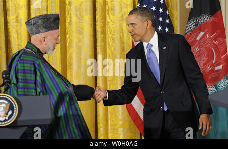 US President Barack Obama (R) shakes hands with Afghan President Hamid Karzai at the conclusion of  a press conference in the East Room of the White House, January 11, 2013, in Washington, DC.  The leaders are discussing a long-term US troop presence as American military forces look at a 2014 withdrawal date from Afghanistan.       UPI/Mike Theiler - Stock Photo