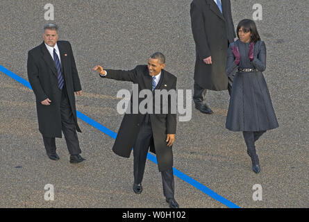 US President Barack Obama and First Lady Michelle Obama accompanied by their Secret Service security detail march past the presidential viewing stand in front of the White House during President Barack Obama's second inauguration in Washington, DC, January 21, 2013.    UPI/Mannie Garcia - Stock Photo