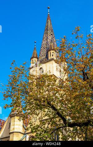 Lutheran Cathedral of Saint Mary steeple behind tree branches, at Sibiu, Romania, Transylvania - Stock Photo