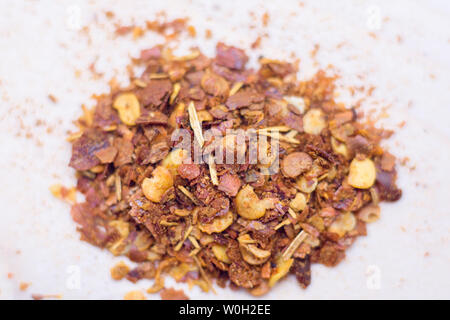 Dried chili flakes and seeds isolated on white background.Pile crushed red cayenne pepper,top view. - Stock Photo