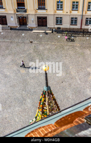 SIBIU, ROMANIA - AUGUST 28, 2017: Unidentified man walks on the Huet Square and his shadow almost touches the top of the turret of Saint Mary Lutheran - Stock Photo