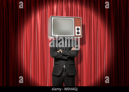 Front crop image of man in suit, with arms folded, and with TV set instead head, standing in spotlight at red stage curtain. - Stock Photo