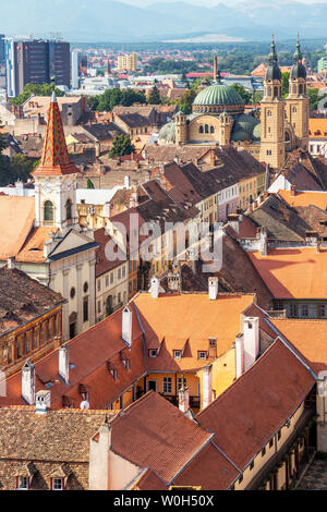 SIBIU, ROMANIA - AUGUST 28, 2017: Sibiu elevated cityscape with Holy Trinity Cathedral and the Reformed Church seen from the steeple of the Lutheran C - Stock Photo