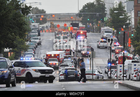 Emergency vehicles line the street near the Navy Yard, a huge complex of buildings located along the Anacostia River waterfront on September 16, 2013 in Washington, DC. A gunman killed at least four and wounded others before being killed by police in a running gun battle.     UPI/Kevin Dietsch - Stock Photo