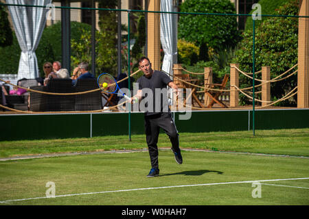 Stoke Poges, Buckinghamshire, UK. 27th June, 2019. Actor Jason Isaacs plays a fun tennis game with world number six Stefanos Tsitsipas (GRE) on day three of The Boodles at Stoke Park Country Club, Hotel and Spa. Credit: Maureen McLean/Alamy Live News - Stock Photo