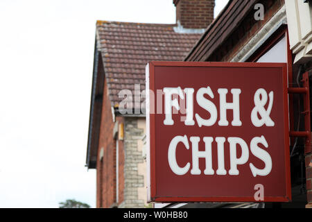 Ashtead, Surrey, UK - Sign for British Fish & Chips hanging on a wall outside Superfish chip shop in daytime - Stock Photo
