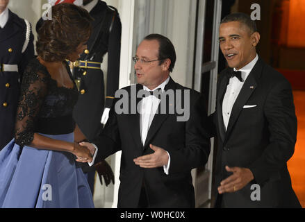 US President Barack Obama (R) and First Lady Michelle Obama welcome French President Francois Hollande for a State Dinner at the White House, February 11, 2014, in Washington, DC. Hollande is on a State Visit to strengthen bilateral, trade, economic and security ties.       UPI/Mike Theiler - Stock Photo
