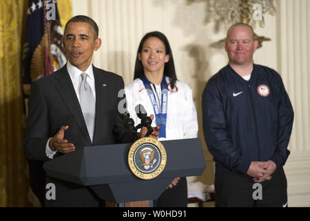 President Barack Obama (L) delivers remarks alongside Olympic Women's Ice Hockey forward and 2014 Winter Olympic Games Closing Ceremony Team USA Flag Bearer Julie Chu and Paralympic Alpine Skier, former US Marine Corps Sergeant and 2014 Winter Paralympic Games Opening Ceremony Team USA Flag Bearer Jon Lujan, during a ceremony where the Obama's welcomed Team U.S.A. to the White House in Washington DC, on April 3, 2014. UPI/Kevin Dietsch - Stock Photo