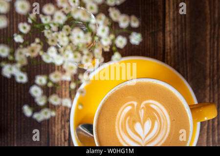 Latte coffe in bright yellow cup and saucer next to some flowers on a wooden table - Stock Photo
