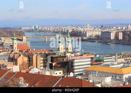 View of Budapest divided by the Danube river and connected by the Margaret Bridge (one of many vehicle and pedestrian bridges across the Danube). - Stock Photo