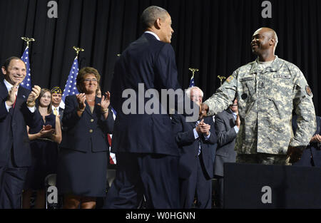 U.S. President Barack Obama (C) shakes hands with US Army Sgt. Major James McGruder, as Veterans Affairs Secretary Robert McDonald (L) applauds prior to Obama signing HR 3230, The Veterans' Access to Care through Choice, Accountability and Transparency Act of 2014, August 7, 2014, at Fort Belvoir, Virginia. The bill aims to assist military veteran's health care by streamlining the VA's bureaucracy in such areas as appointments and training of staff and personnel at VA medical care facilities.               UPI/Mike Theiler - Stock Photo