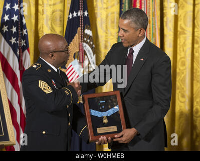 U.S President Barack Obama awards the Medal of Honor posthumously to two World War I soldiers Army Private Henry Johnson and Sergeant William Shemin in a ceremony in the East Room of the White House in Washington, DC on June 2, 2015.   Command Sergeant Major Louis Wilson of the New York National Guard shakes hands with Obama after accepting on behalf of Private Johnson.       Photo by Pat Benic/UPI - Stock Photo