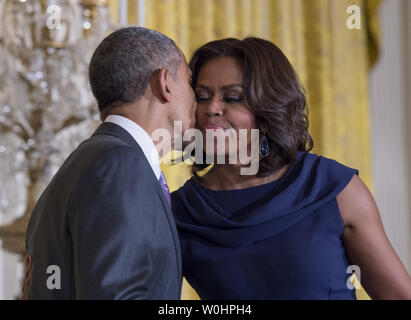 President Barack Obama kisses first lady Michelle after delivering remarks during an event on expanding efforts to help adolescent girls worldwide attend and stay in school, at the White House in Washington DC, March 3, 2015.  Photo by Molly Riley/UPI - Stock Photo