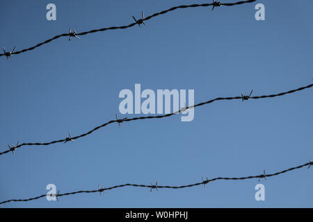 Three rows of rusty barbed wire in front of a blue sky, abstract - Stock Photo