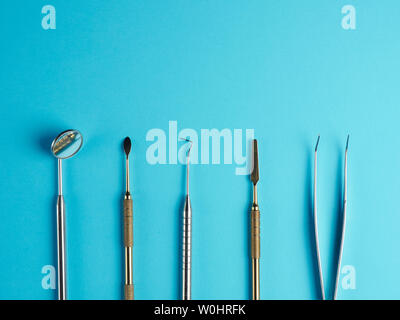 Professional dental tools on blue background - Stock Photo