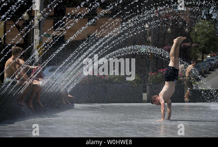 People cool off in a fountain at the Georgetown Waterfront Park as temperatures top out in the mid 90's for the second day in a row, in Washington, D.C. on June 12, 2015. The Nation's Capital is in the middle of a mini heatwave as summer temperatures are expected to stay high though the weekend. Photo by Kevin Dietsch/UPI - Stock Photo