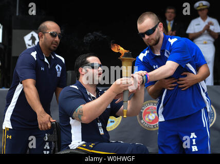 Navy's Austin Reese with escort Adrian Mohammed (right) hands the torch to Air Force athlete Kevin O'Brien held by escort Jennifer Stone (obscured), during the torch relay at the opening ceremony of the 2015 Department Of Defense Warrior Games at the United States Marine Corps base in Quantico, Va.,  June 19, 2015.  Photo by Molly Riley/UPI - Stock Photo