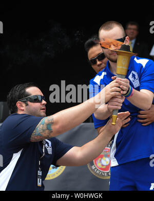 Navy's Austin Reese hands the torch to Air Force athlete Kevin O'Brien held by escort Jennifer Stone (obscured), during the torch relay at the opening ceremony of the 2015 Department Of Defense Warrior Games at the United States Marine Corps base in Quantico, Va.,  June 19, 2015.  Photo by Molly Riley/UPI - Stock Photo