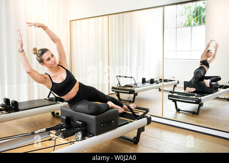 Woman making mermaid yoga exercise on reformer pilates bed reflecting in the mirror - Stock Photo