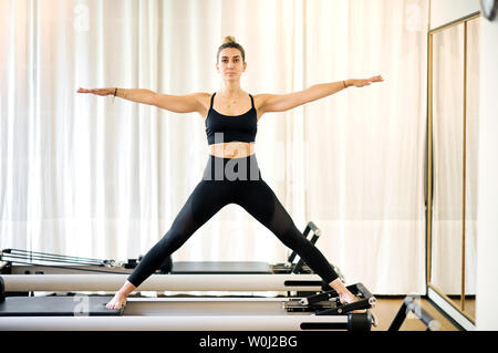 Single fit woman doing yoga standing with arms and legs spread on reformer bed. White curtain in background. - Stock Photo