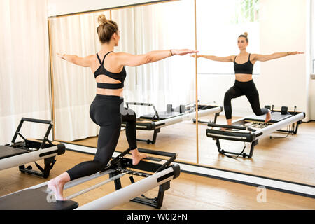 Individual woman in black doing lunge stretch pilates series while standing on reformer bed in workout room - Stock Photo