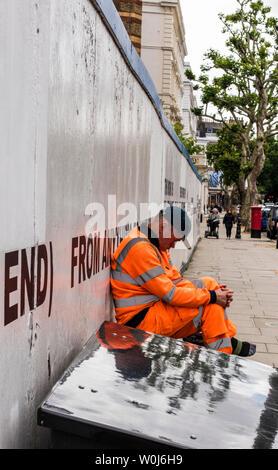 Workman taking a break outside construction site hoarding, London, England, UK - Stock Photo
