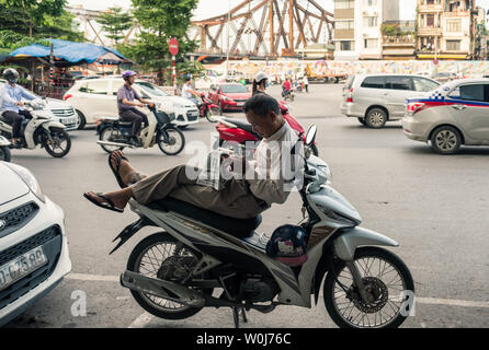 Hanoi, Vietnam - Sep 10 2017 : Vietnamese uncle sitting on motorcycle with reading newspaper and traffic jam on road - Stock Photo