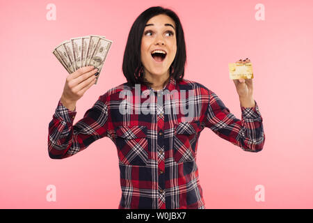 Photo of happy young woman standing isolated over pink background. Looking aside holding money and credit card. - Image - Stock Photo