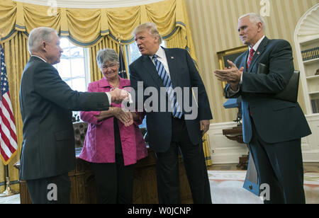 President Donald Trump shakes hands with Attorney General Jeff Sessions after Vice President Mike Pence (R) sworn him in during a ceremony, Sessions' wife Mary also attended, during a ceremony in the Oval Office at the White House in Washington, D.C. on February 9, 2017. Sessions was confirmed last night by the Senate in a nearly-party-line vote of 52 to 47. Photo by Kevin Dietsch/UPI - Stock Photo